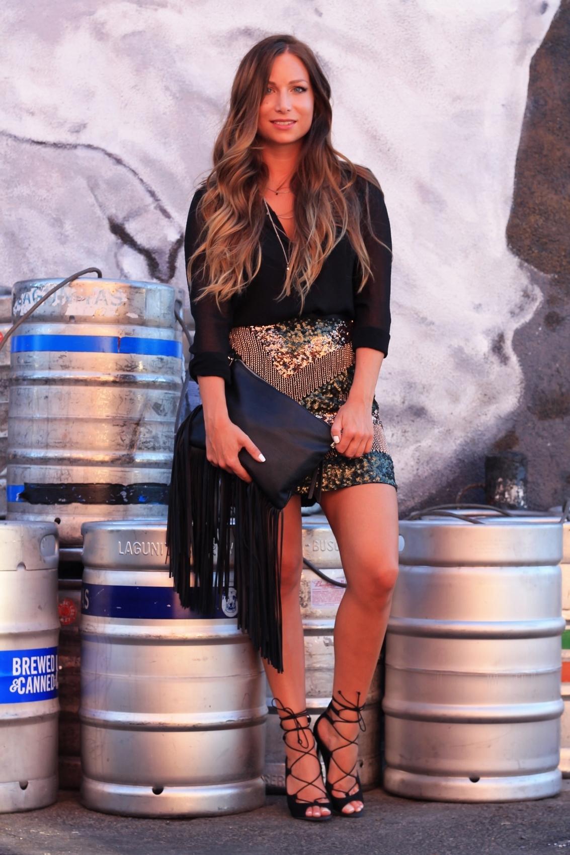 jupe à paillettes h&m et chemisier noir transparent sandales à talon pochette à franges